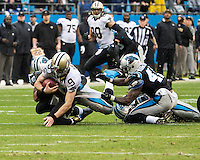 The Carolina Panthers played the New Orleans Saints for supremacy in the NFC South.  December 22, 2013 at Bank of America Stadium.  The Panthers scored the winning touchdown with 23 seconds left in the game to give them the opportunity to clinch the NFC South with a win next week.  New Orleans Saints quarterback Drew Brees (9) is sacked by Carolina Panthers cornerback Captain Munnerlyn (41) and Carolina Panthers defensive end Greg Hardy (76)