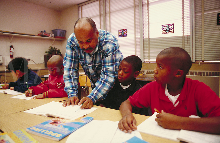 TEACHER HELPING INDIVIDUAL STUDENTS IN CLASS. ELEMENTARY SCHOOL STUDENTS. OAKLAND CALIFORNIA USA CARL MUNCK ELEMENTARY SCHOOL.