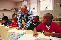 TEACHER HELPING INDIVIDUAL STUDENTS IN CLASS. ELEMENTARY SCHOOL STUDENTS. OAKLAND CALIFORNIA USA CARL MUNCK ELEMENTARY SCHOOL.
