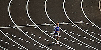 A young boy runs on a track during a running competition in a track and field event