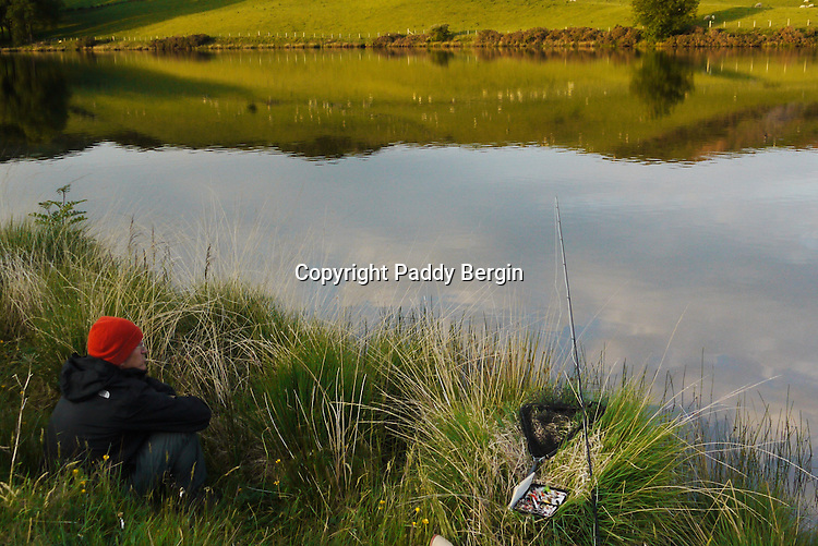 This photo was taken at Llyn Frongoch in close proximity to the village of Trisant, close to the Aberystwyth to Devil's Bridge road. Frongoch is a fly only lake and is regularly stocked with both brown and rainbow trout. The quality of fish is excellent and boats are available. At Frongoch, Aberystwyth Angling Association have two caravans for hire for visitors wishing to stay in the area and take advantage of the fishing in this small but delightfully situated lake. Admist wonderful upland scenery, close to the Rheidol and Ystwyth valleys, and just twelve miles from the coast at Aberystwyth they represent excellent value for anyone wishing to combine angling with a family holiday. Taking a break and enjoying the view of the lake. <br /> <br /> Stock Photo by Paddy Bergin
