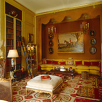 A long banquette covered in golden-yellow brocade takes up an entire wall of the library and the equestrian painting is a portrait of the Duke of Windsor by Sir Alfred Munnings