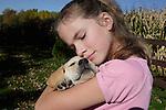 12 year old girl hugs ( a little too hard) a yellow Labrador retriever puppy (AKC).  Fall.  Birchwood, WI