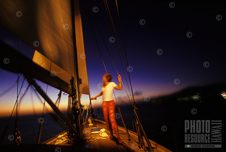 Woman trimming sails just after sunset on sailboat off Makua Beach, West Side Oahu