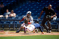 Jacksonville Jumbo Shrimp catcher Rodrigo Vigil (1) fields a throw as Drew Waters (3) scores the game winning run on a squeeze play with umpire Jose Navas looking on to make the call during a Southern League game against the Mississippi Braves on May 5, 2019 at Trustmark Park in Pearl, Mississippi.  Mississippi defeated Jacksonville 1-0 in ten innings.  (Mike Janes/Four Seam Images)