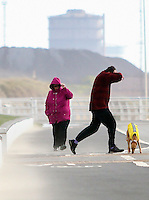 WEATHER PICTURE WALES Thursday 23 February 2017<br />Walkers brave high winds and whipping sands at Aberavon Beach, Port Talbot, Wales, UK