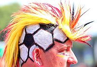 A Germany fan with a football painted on his head