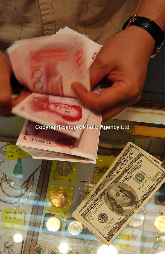 A man exchanges Renminbi for US$ at a small money changers in Hong Kong. The U.S. and many Western nations have been arguing that the Renminbi is undervalued giving the chinese an advantage in an already difficult playing field that is already tilted in favour of China..