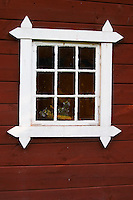 A window with flowers in the old barn building with a carpentry shop that Astrid Lindgren used as model for many of her stories. Nas. Vimmerby town Smaland region. Sweden, Europe.