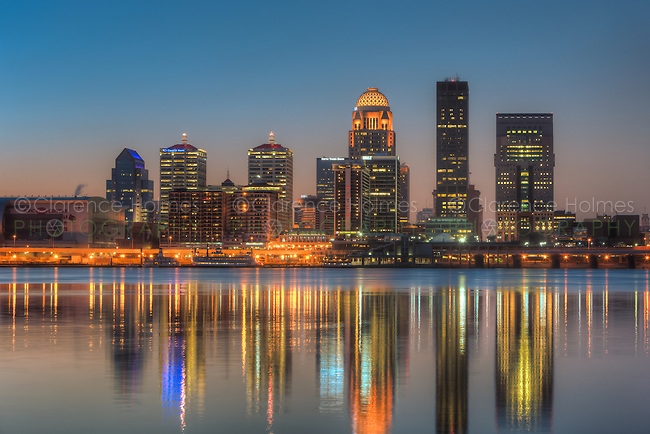 The illuminated skyline of Louisville, Kentucky reflects off the calm surface of the Ohio River under a clear sky during morning twilight shortly before sunrise.