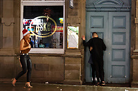 A young couple kiss in a doorway in Wind Street, Swansea, Wales  on Mad Friday, Booze Black Friday or Black Eye Friday, the last Friday night before Christmas Day, when traditionally people in the UK go out to celebrate the start of their holidays. Friday 22 December 2017