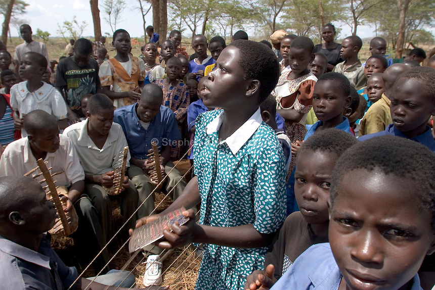 Empowering Victims of War- Praise and worship at the open air Grace Community Church. The church gives a place for fellowship to the surrounding community. Canaan Family Farm lends land to displaced people from the Northern conflict to have them learn the benefits of work and empowerment. Rwakayata, Masindi, Uganda, Africa. December 2005 © Stephen Blake Farrington