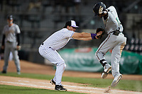Liover Peguero (10) of the Greensboro Grasshoppers avoids the tag attempt of Winston-Salem Dash first baseman AJ Gill (7) at Truist Stadium on June 15, 2021 in Winston-Salem, North Carolina. (Brian Westerholt/Four Seam Images)