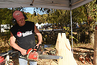 """CRAFTS BESIDE THE CREEK<br />Scott Winford of Greenwood shapes a chain-saw carving of a wolf on Wednesday Oct. 14 2020 at the 14th annual Spanker Creek Farm arts and crafts fair. Winford sells wide selection of chain-saw carvings at his booth. The fair runs through Sunday at the farm on McNelly Road one-half mile east of U.S. 71 near Bentonville and Bella Vista. Admission is free. The """"It's Fall Y'all"""" crafts fair starts to day at the Benton County fairgrounds. Go to nwaonline.com/201015daily/ to see more photos.<br />(NWA Democrat-Gazette/Flip Putthoff"""