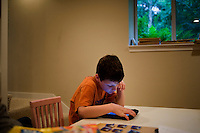 """Jack Ursitti, age 7, uses an iPad to play a spelling game in his home in Dover, Mass., on Monday, July 25, 2011. The game asks Jack to spell three-letter words that accompany pictures. Jack has been diagnosed with autism.  After school at his home, Jack works with his teacher and a therapist to do educational and independent leisure activities. ..Jack received an iPad for Christmas, according to his mother Judith Ursitti. """"I wanted mine back,"""" said Judith. She had gotten an iPad for her birthday in 2010, and Jack used it constantly. """"There's something intuitive about it,"""" said Judith.  In the beginning it was just a distraction, """"but now we're moving to use it for an educational purpose,"""" she said...Jack Ursitti wears a small GPS ankle bracelet at all times in case he runs off from his family or caretakers. The device will be activated if he goes missing, allowing police and other searchers to find him."""