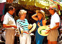 Generational couples at a Caribbean market, buying hats