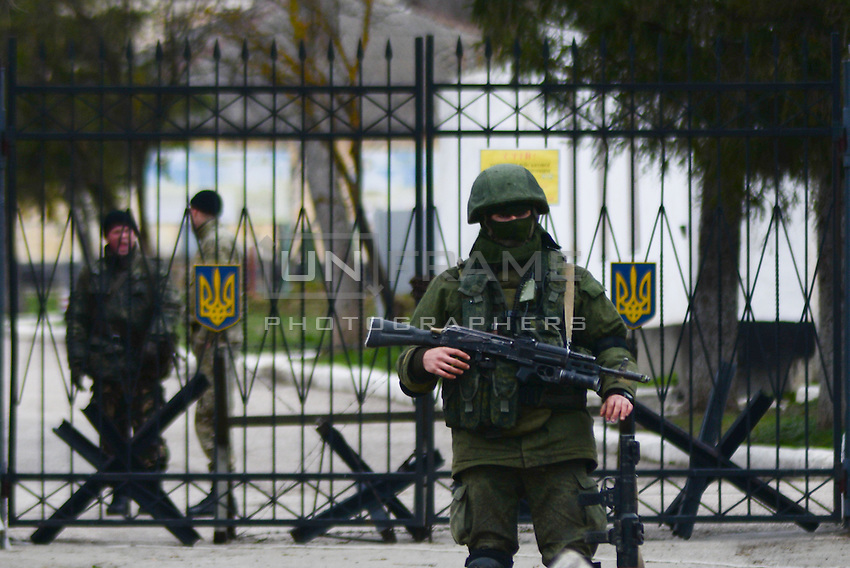 Soldier in Russian uniform secures the perimeter of the occupied Ukrainian military base in Perevalnoe