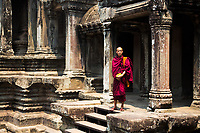 Bayon Temple monk standing in red robe in the famous, ancient UNESCO heritage Khmer Angkor Wat temple, Siem Reap, Cambodia Southeast Asia