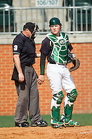 Charlotte 49ers catcher Patric King (28) looks to the dugout for the sign as home plate umpire Barry Chambers adjusts his clicker during the game against the Canisius Golden Griffins at Hayes Stadium on February 23, 2014 in Charlotte, North Carolina.  The Golden Griffins defeated the 49ers 10-1.  (Brian Westerholt/Four Seam Images)