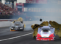 Feb 7, 2015; Pomona, CA, USA; NHRA funny car driver Jeff Arend (left) blows an engine on fire alongside Robert Hight during qualifying for the Winternationals at Auto Club Raceway at Pomona. Mandatory Credit: Mark J. Rebilas-