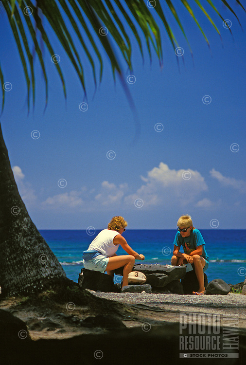 A woman and a boy play a game with stones at Puuhonua O Honaunau, Big Island's City of Refuge