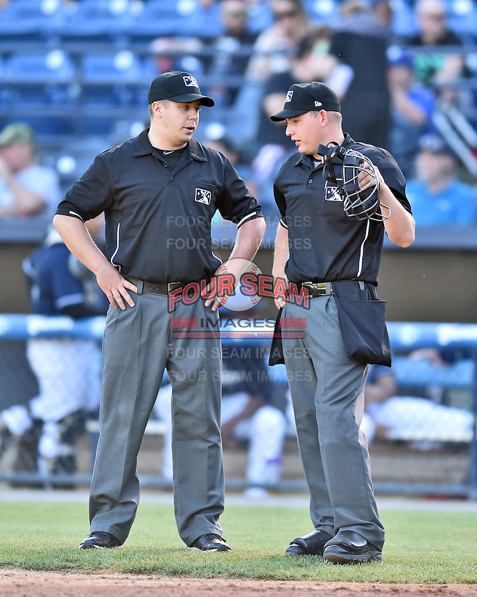 First base umpire Matt Carlyon and home plate umpire Ryan Powers talk between innings of the South Atlantic League game between the Hagerstown Suns and the Asheville Tourists at McCormick Field on April 28, 2016 in Asheville, North Carolina. The Tourists were leading the Suns 6-5 when the game was delayed in the top of the 6th inning due to darkness. (Tony Farlow/Four Seam Images)