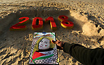 A Palestinian man hold a portrait of Ahed Tamimi, 16-year-old prominent campaigner against Israel's occupation and who is currently detained, at a beach in Gaza City on December 31, 2017 on the last day of the year. Photo by Ashraf Amra