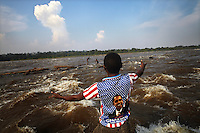 A man wearing a shirt decorated with the Stars and Stripes and a picture of US President Barack Obama, gestures to fishermen at Boyoma Falls (known locally as Wagenia Falls). This is the last of seven cataracts below which the Lualaba River becomes the Congo. For generations members of the Wagenia tribe have fished here using great wooden scaffolds and traps in the same manner described by Henry Morton Stanley, after whom the falls were also once named, during his navigation of the Congo in 1874-77.