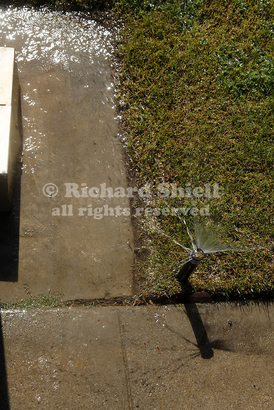 SPRINKLER OVERSPRAYING ONTO CONCRETE
