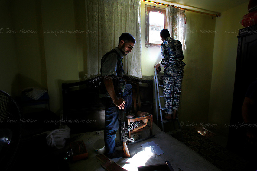 Free Syria Army soldiers look out the window of one of their many fighting positions prior to attacking a building housing several Assad forces during urban fighting in the Salah-al-Din neighborhood of Aleppo. ..© Javier Manzano.