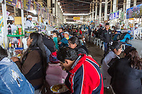 Peru, Cusco, San Pedro Market.  People Eating in the Food Court Area of the Market.