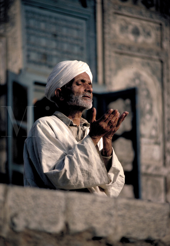 Turbaned man praying at the mosque in Srinagar, Kashmir. Muslim prayers are required to be said five times a day, facing Mecca. Srinagar is the capital of Kashmir, a disputed territory of South Asia, administered since 1972 as a predominantly Muslim state