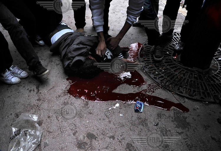 A protester dies on the pavement after a shot in the head. Protests against former prime minister Mohamed Ghannouchi, who took control after the ousting of president Zine El Abidine Ben Ali, turned violent and left at least one dead and several wounded as soldiers used live ammunition and teargas against the protesters..