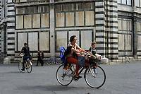Ciclisti in piazza San Giovanni, vicino al Battistero. Cyclists in Piazza San Giovanni, near the Baptistery..
