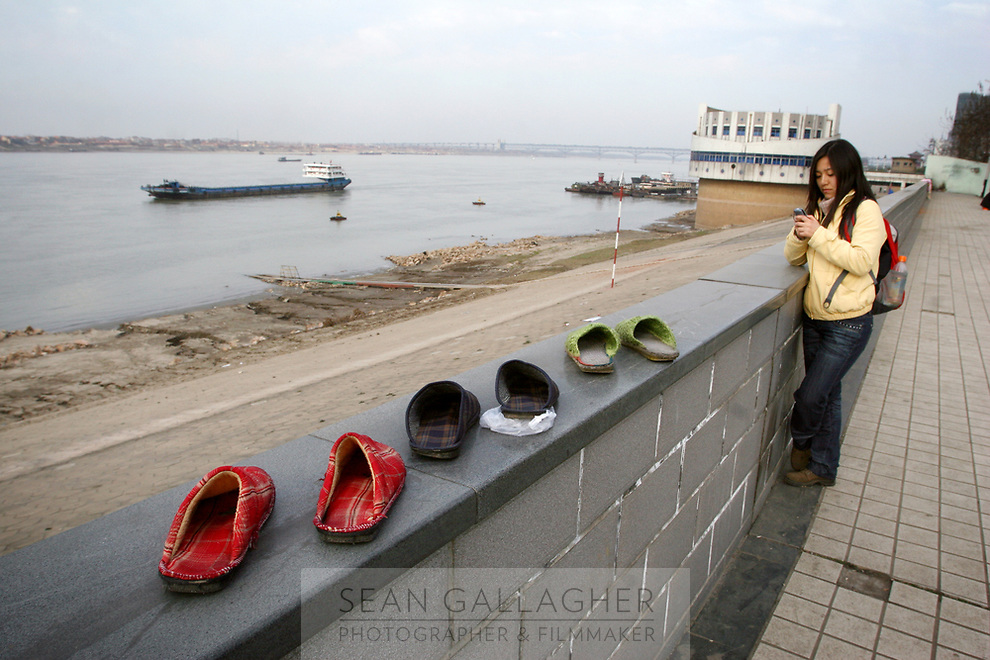 CHINA. Jiangxi Province.  Jiujiang. Shoes sitting on a wall to dry next to he Yangtze river. Jiujiang is a city of 4.6 million people, located on the southern shore of the Yangtze River. The Yangtze River is reported to be at its lowest level in 150 years as a result of a country-wide drought. It is China's longest river and the third longest in the world. Originating in Tibet, the river flows for 3,964 miles (6,380km) through central China into the East China Sea at Shanghai.  2008