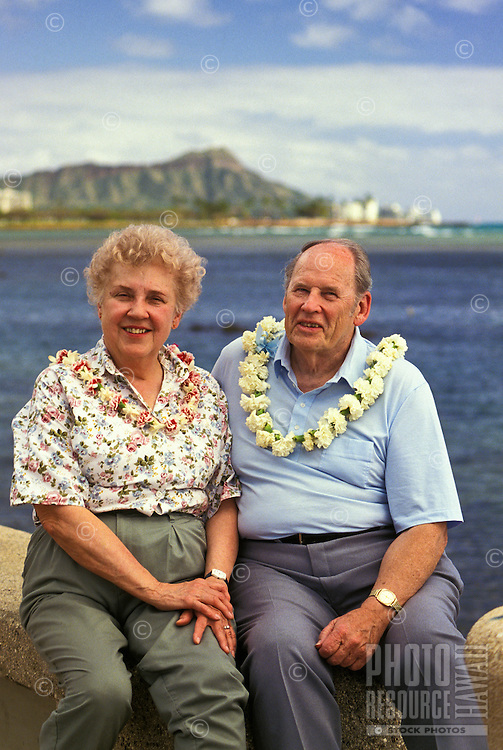 retired couple wearing flower lei at Kakaako Waterfront Park, with Diamond Head in the distance