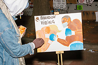 Jerome Sudi (@paradisevibing) paints a pictures of Donald Trump getting hit in a boxing match with a black man as demonstrators gather in Black Lives Matter Plaza near the White House on the night of Election Day in Washington, D.C., on Tue., Nov. 3, 2020. Election results remained uncertain late into the night and demonstrators were peaceful.