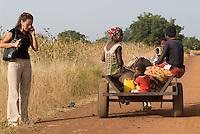 BURKINA FASO, western woman with cellular phone beside african family on donkey cart / Burkina Faso westliche Frau mit Mobiltelefon neben afrikanischer Familie auf Eselskarren auf Landstrasse