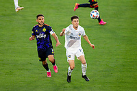 CARSON, CA - JUNE 19: Cristian Roldan #7 of Seattle Sounders FC and Jorge Villafana #19 of the Los Angeles Galaxy get after a loose ball during a game between Seattle Sounders FC and Los Angeles Galaxy at Dignity Health Sports Park on June 19, 2021 in Carson, California.