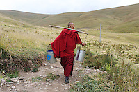 A Tibetan monk carries water cans toward a river on the grasslands. The water is for the local monastery in Sershul, in Sichuan Province on the Tibetan Plateau. The Sanjiangyuan or Three Rivers Headwater region of western China contains the sources of the Yangtze, Mekong and Yellow Rivers.