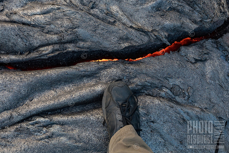 A professional photographer demonstrates how dangerously close he sometimes gets to molten lava to capture images like this one in Pulama Pali, Hawai'i Volcanoes National Park, Hawai'i Island, December 2017.