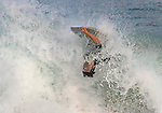 A boarder flips around on a wave at Sandy Beach in Hawaii.