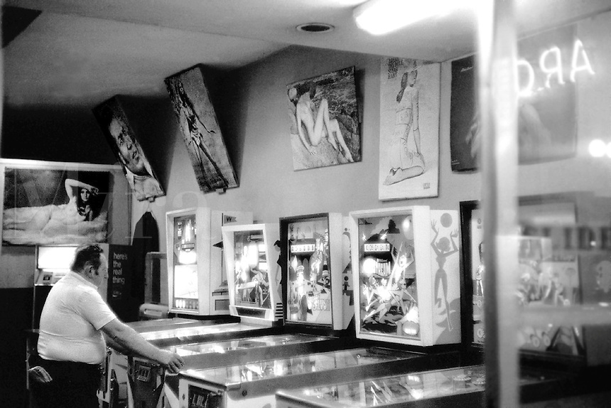Man, alone, playing pinball at night in run down arcade decorated with popular girlie posters. Houston Texas USA.