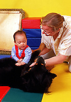A teaching assistant helps an infant participate in pet therapy.