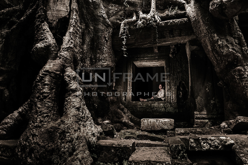 UNESCO World Heritage Site,  the ruins of the Ankgor wat temples. A child sits on an Khmer architectural element that is being swallowed by  the roots of secular forest trees.    Local children  usually make their living by selling crafts and other products to tourists.   Seam Reap, Cambodia.