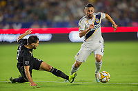 CARSON, CA - SEPTEMBER 15: Sebastian Lletget #17 of the Los Angeles Galaxy moves past Graham Zusi #8 of Sporting Kansas City during a game between Sporting Kansas City and Los Angeles Galaxy at Dignity Health Sports Park on September 15, 2019 in Carson, California.