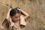 A male portrait of a young Native American Sioux Indian boy fixing his braids outside in South Dakota during the fall season