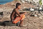 A boy sits on the shore on the remote island of Kiritimati in Kiribati