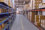 Commercial photo of warehouse interior, showing shelving with inventory in boxes