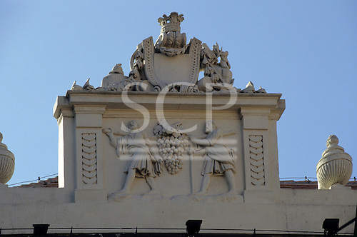 Bratislava, Slovakia; pediment on top of a building depicting two men carrying a huge bunch of grapes on a pole.
